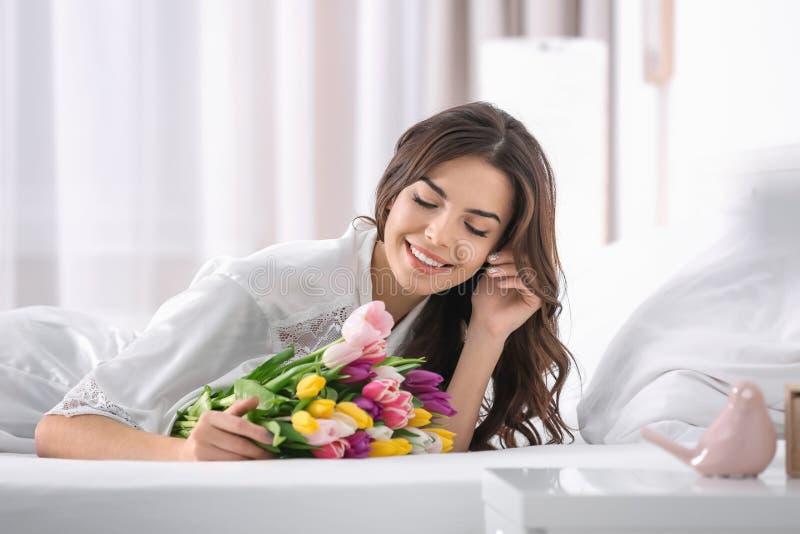 Bella donna con il mazzo dei tulipani sul letto fotografia stock libera da diritti