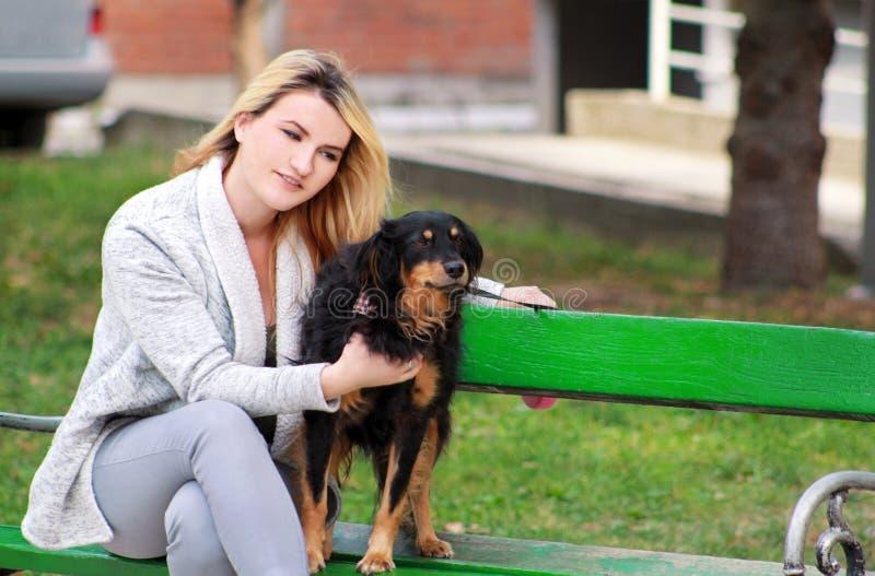 Bella donna con il suo piccolo cane misto della razza che si siede e che posa davanti alla macchina fotografica sul banco di legn fotografia stock