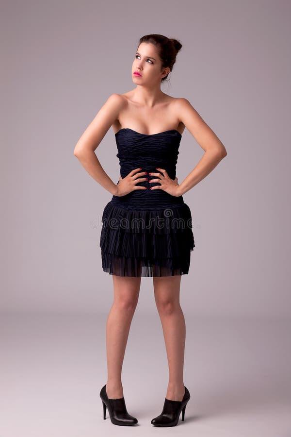 Bella donna con il vestito elegante, pensante immagini stock