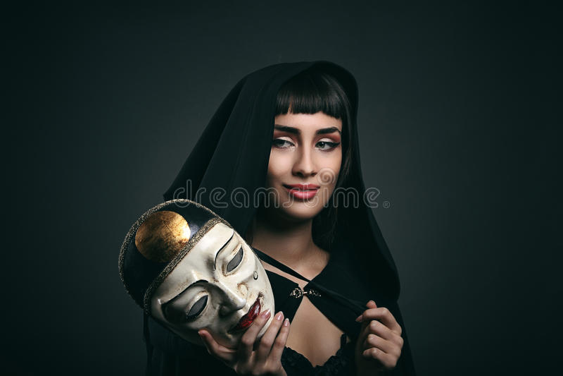 Bella donna con l'abito e la maschera neri immagini stock
