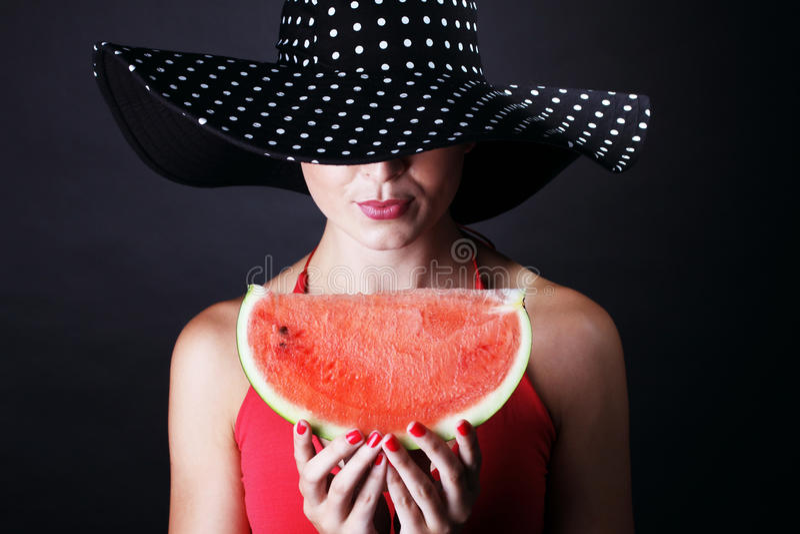 Bella donna con l'anguria ed il cappello su fondo nero fotografia stock