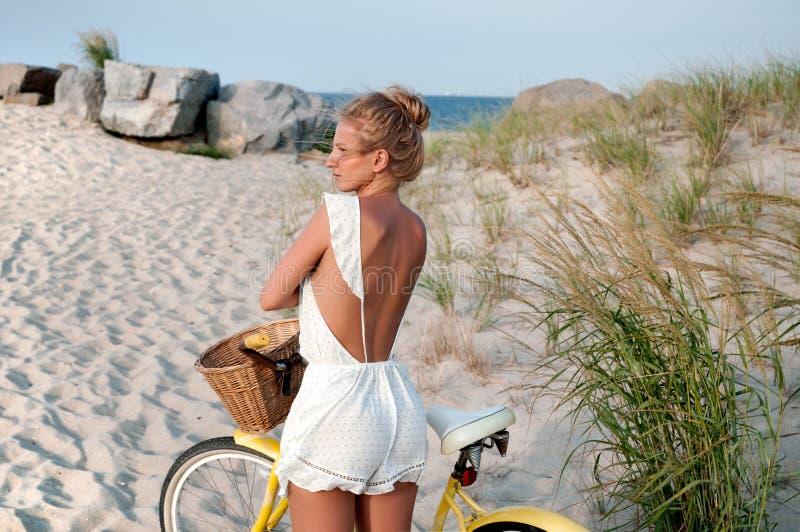 Bella donna con la bici sulla spiaggia fotografia stock