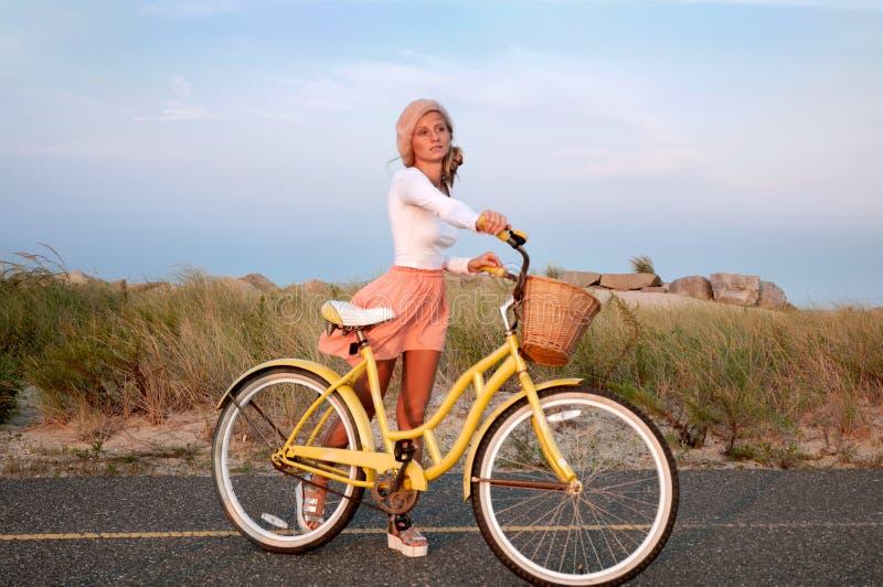 Bella donna con la bici sulla spiaggia fotografia stock libera da diritti