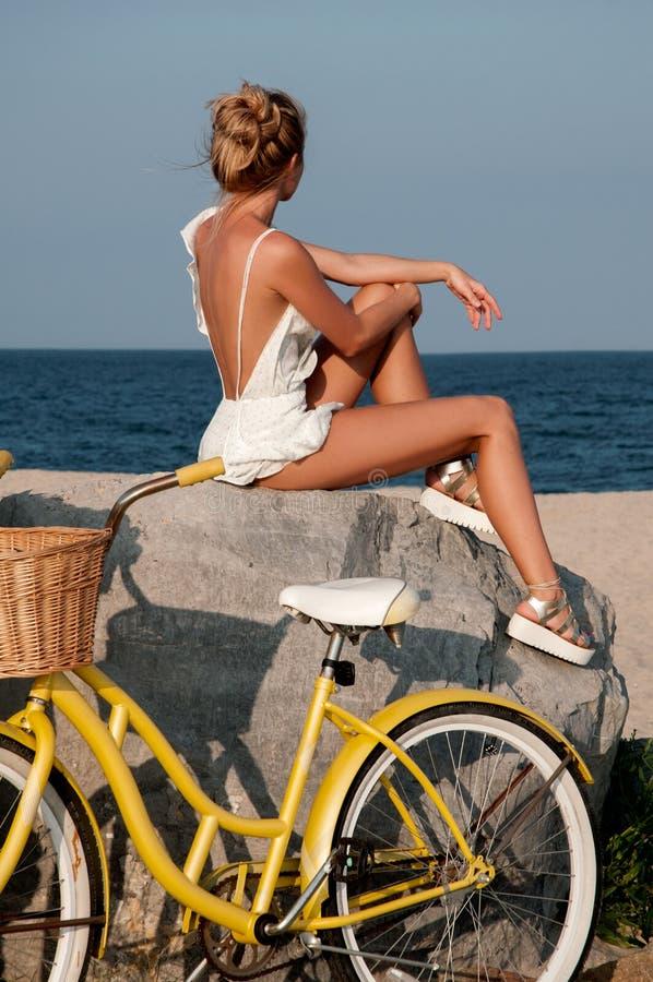Bella donna con la bici sulla spiaggia immagine stock libera da diritti