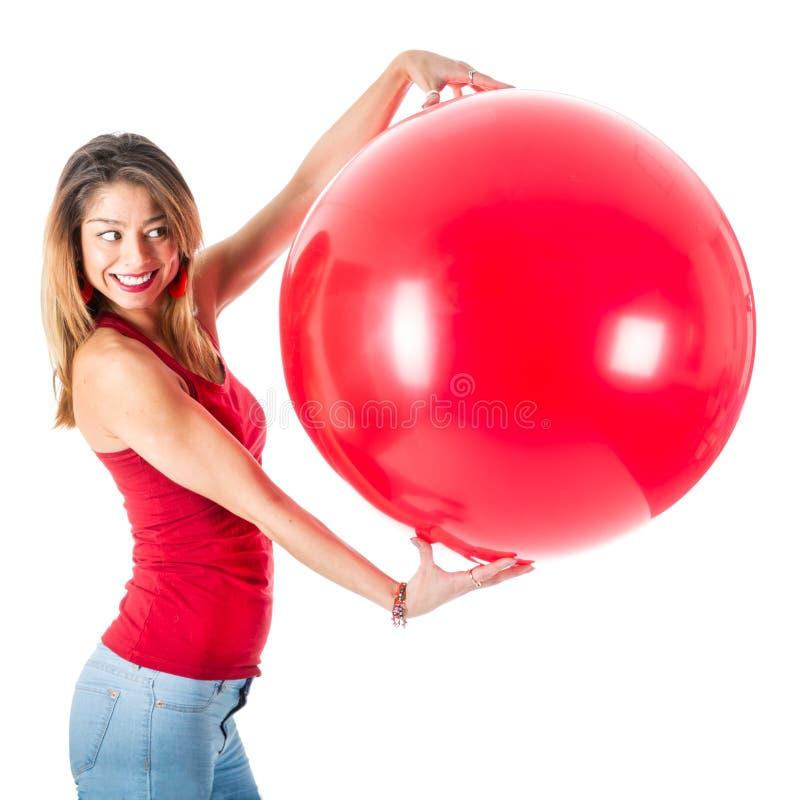 Bella donna con la camicia rossa che tiene un pallone mega fotografia stock libera da diritti