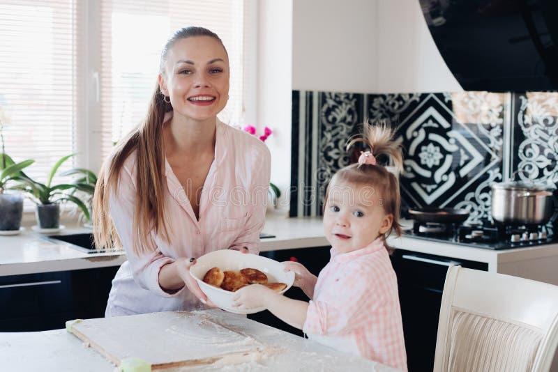 Bella donna con la ciotola adorabile della tenuta del bambino con i biscotti fotografia stock