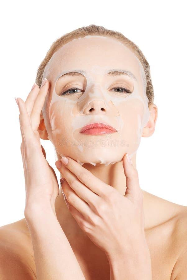 Bella donna con la maschera del collagene sul fronte. immagini stock
