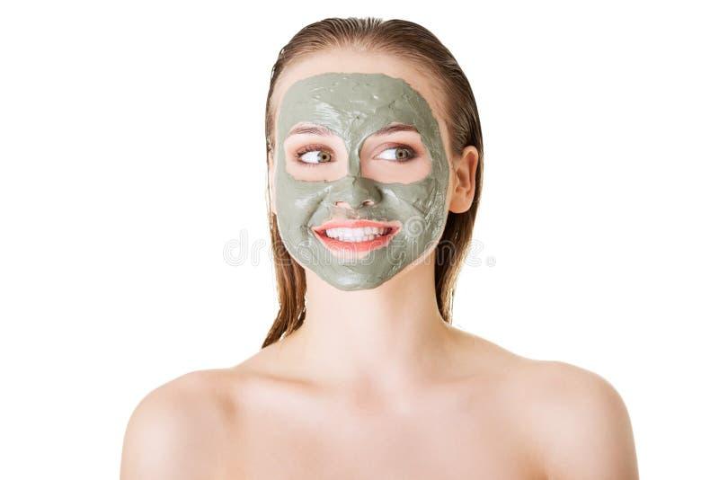 Bella donna con la maschera facciale dell'argilla, isolata su bianco fotografie stock
