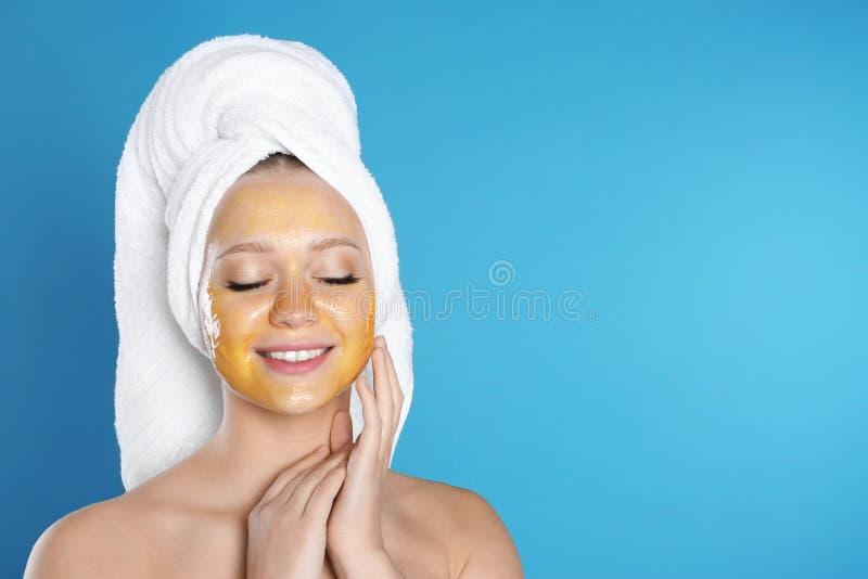 Bella donna con la maschera naturale sul suo fronte contro il fondo di colore fotografie stock libere da diritti