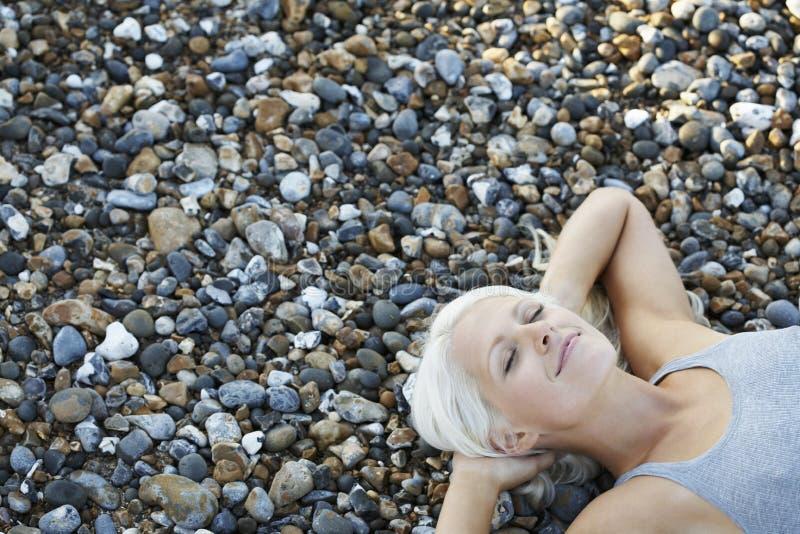 Bella donna con la menzogne chiusa degli occhi sui ciottoli alla spiaggia fotografie stock