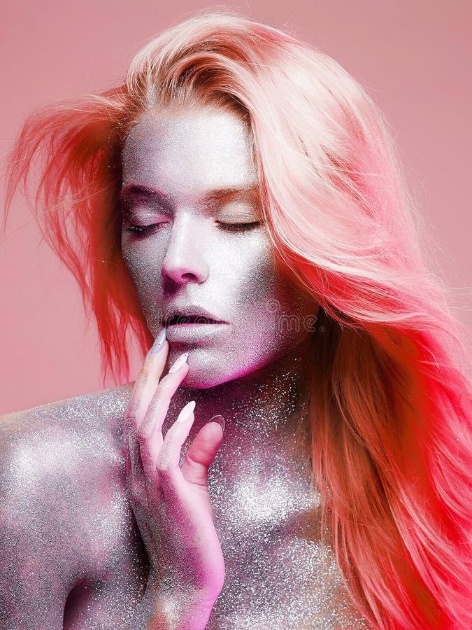 Bella donna con la pelle delle scintille nel colore rosa fotografia stock
