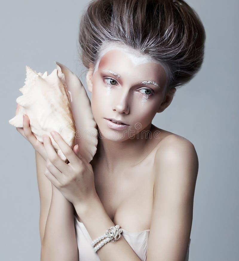 Bella donna con la posizione del seashell. Arte immagini stock libere da diritti