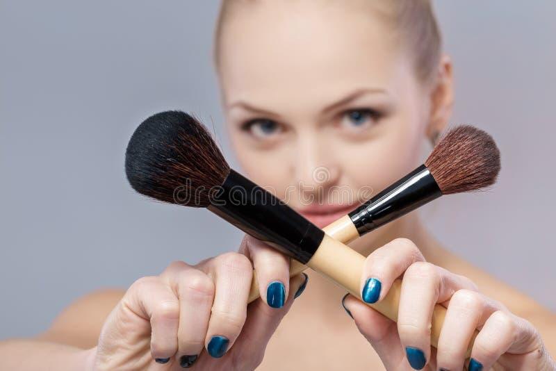 Bella donna con la spazzola naturale di trucco della tenuta di trucco la spazzola è ragazza tagliente e vaga fotografia stock