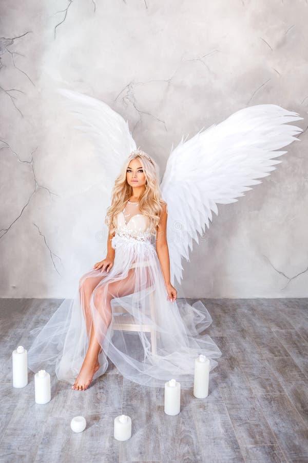 Bella donna con le ali bianche su fondo bianco fotografia stock libera da diritti