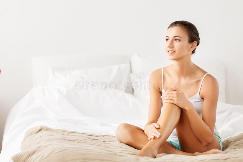 Bella donna con le gambe nude sul letto a casa fotografia stock