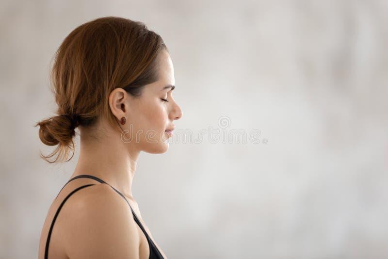 Bella donna con occhi chiusi che pratica yoga, meditazione, vista del profilo fotografia stock libera da diritti