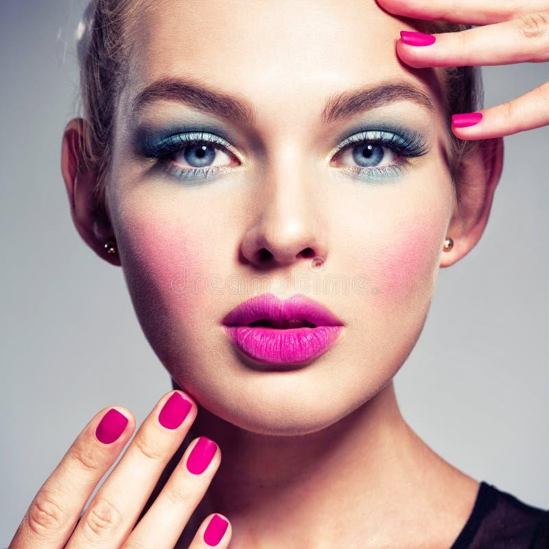 Bella donna con trucco blu degli occhi e dei chiodi rosa immagini stock libere da diritti
