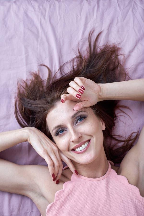 Bella donna con trucco che si trova a letto, ritratto del primo piano fotografie stock libere da diritti