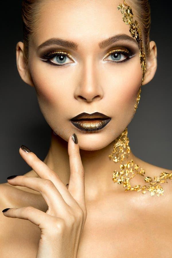 Bella donna con trucco dell'oro immagine stock
