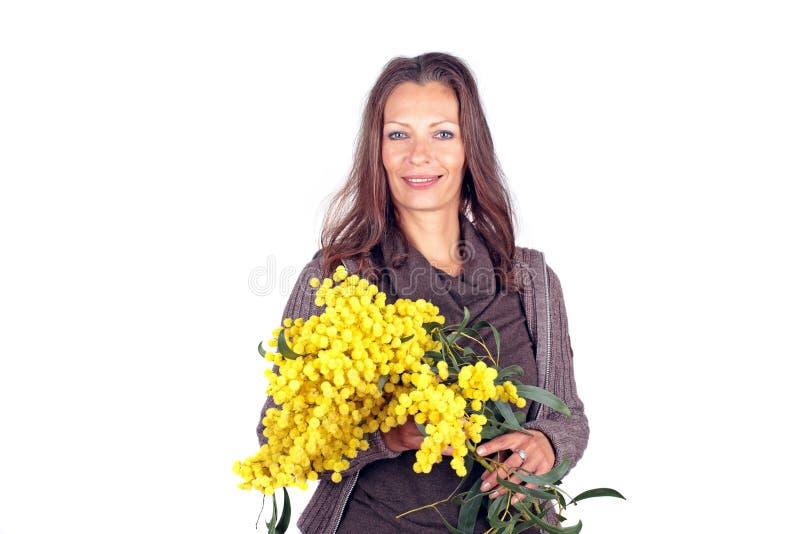 Bella donna con un mazzo della mimosa in primavera immagini stock libere da diritti