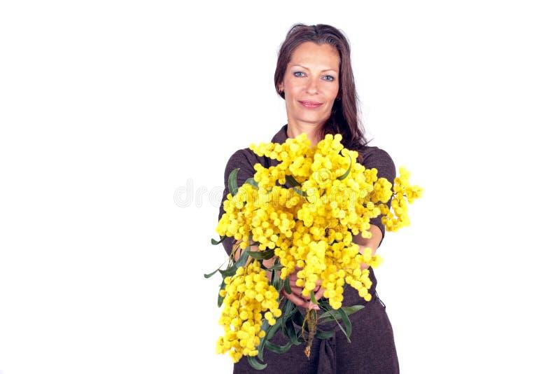 Bella donna con un mazzo della mimosa in primavera immagine stock