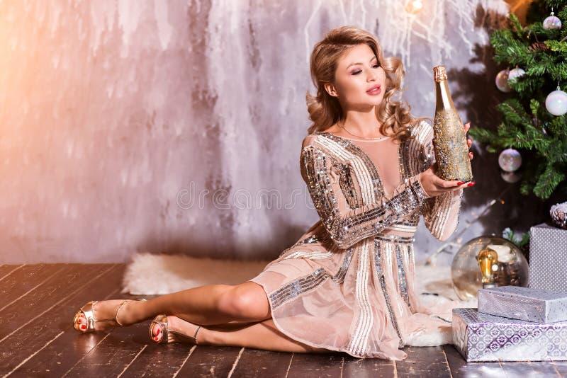 Bella donna con una bottiglia del champagne Giovane signora felice con i regali dei capelli di curlu dal camino vicino all'albero fotografia stock libera da diritti