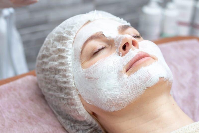 Bella donna con una maschera facciale ad un salone di bellezza fotografia stock libera da diritti