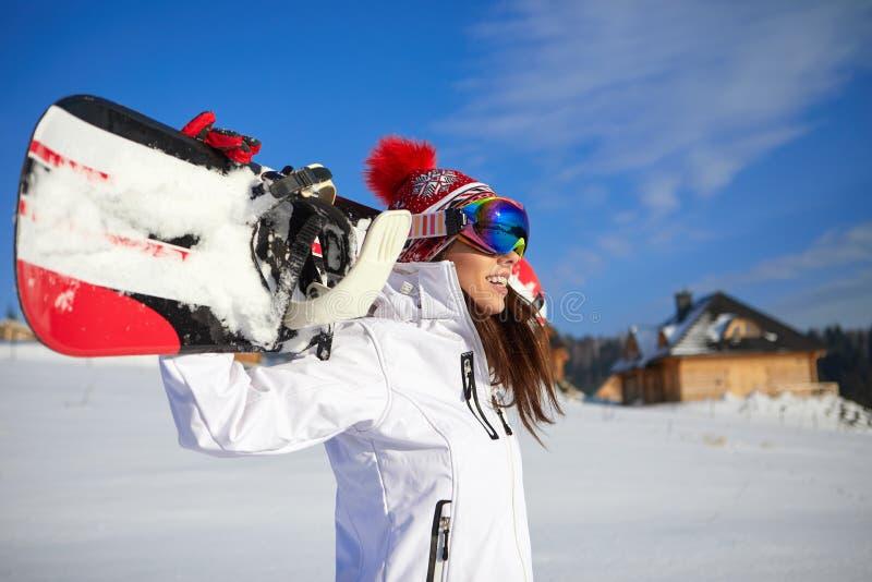 Bella donna con uno snowboard Concetto di sport immagini stock