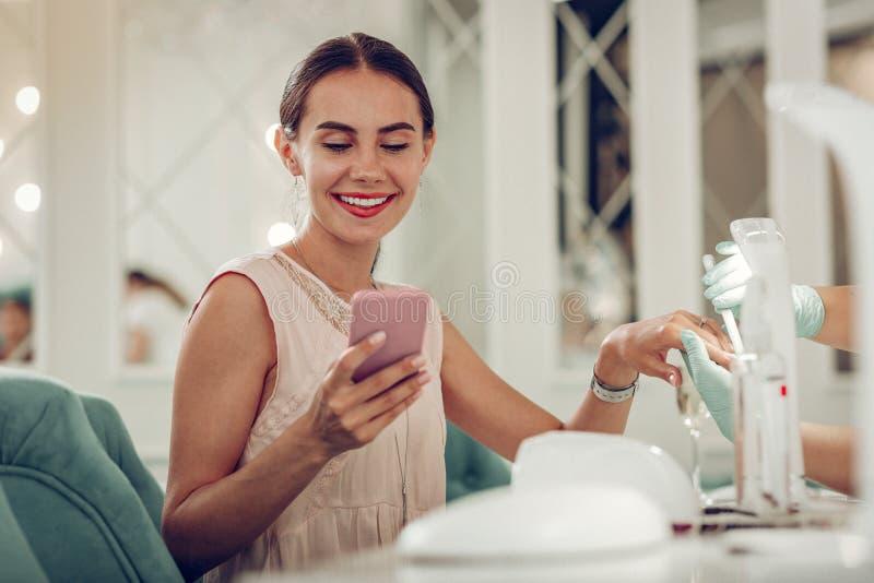 Bella donna contenta di medio evo che controlla il suo smartphone fotografie stock