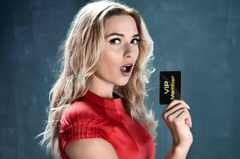 Bella donna contentissima che tiene la carta di VIP fotografia stock libera da diritti