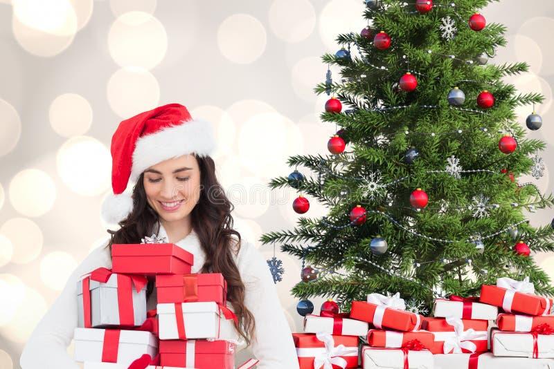 Bella donna in costume di Santa che esamina i regali di natale fotografie stock libere da diritti