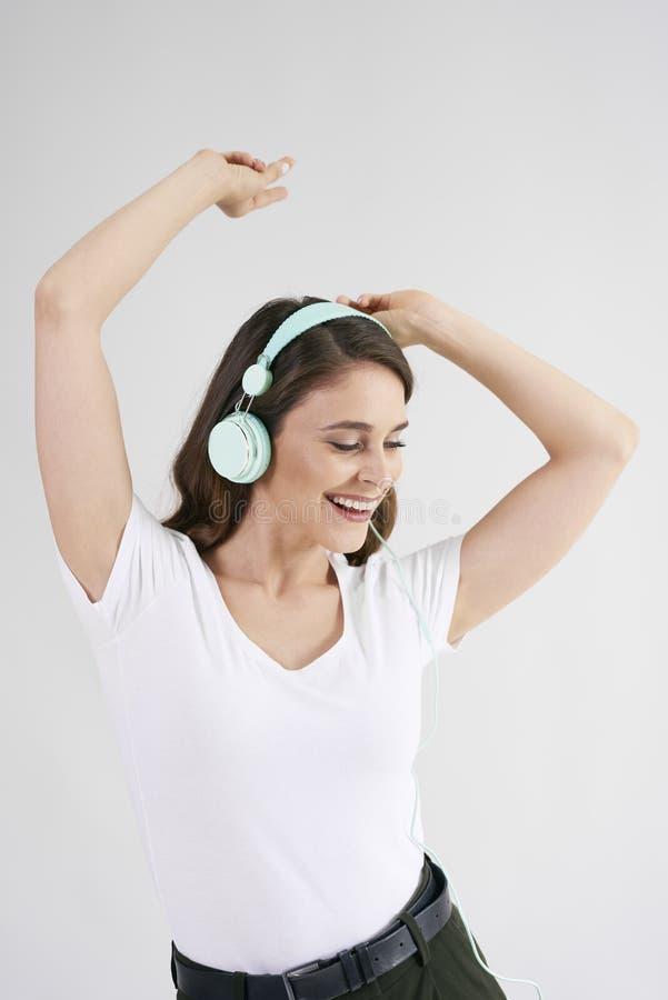 Bella donna in cuffie che ascolta la musica e ballare fotografie stock
