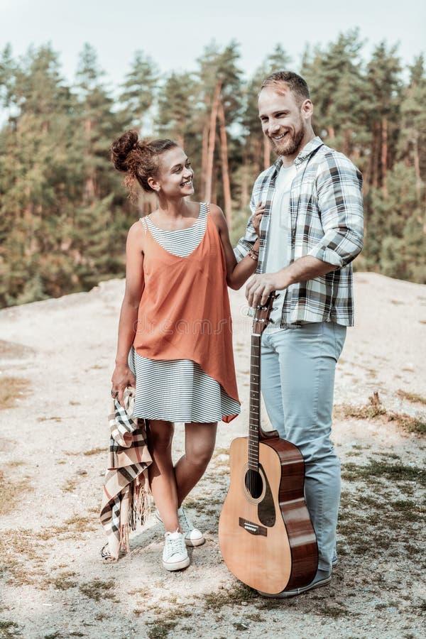 Bella donna d'orientamento con il plaid a disposizione che esamina il suo ragazzo con la chitarra fotografia stock libera da diritti
