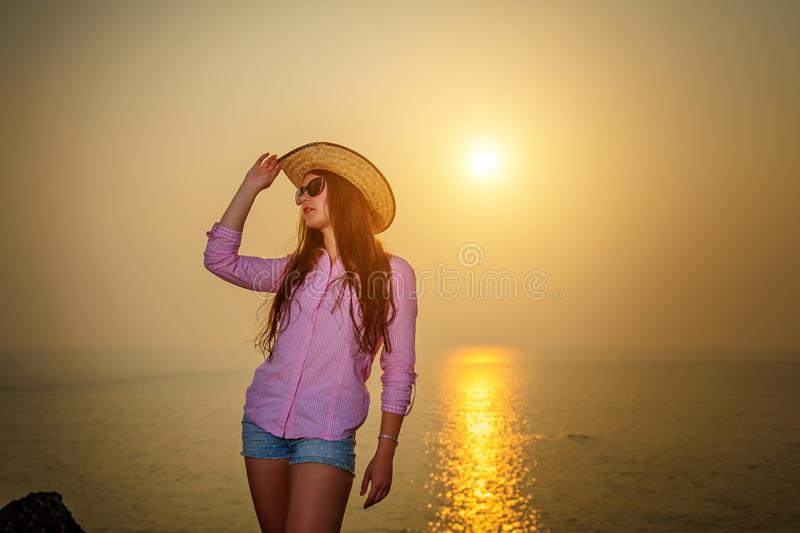 Bella donna dai capelli lunghi contro il tramonto sul mare Ragazza in occhiali da sole che tengono un cappello e che fanno una pa immagine stock