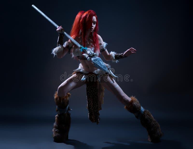 Bella donna dai capelli rossi in abbigliamento di età della pietra immagini stock
