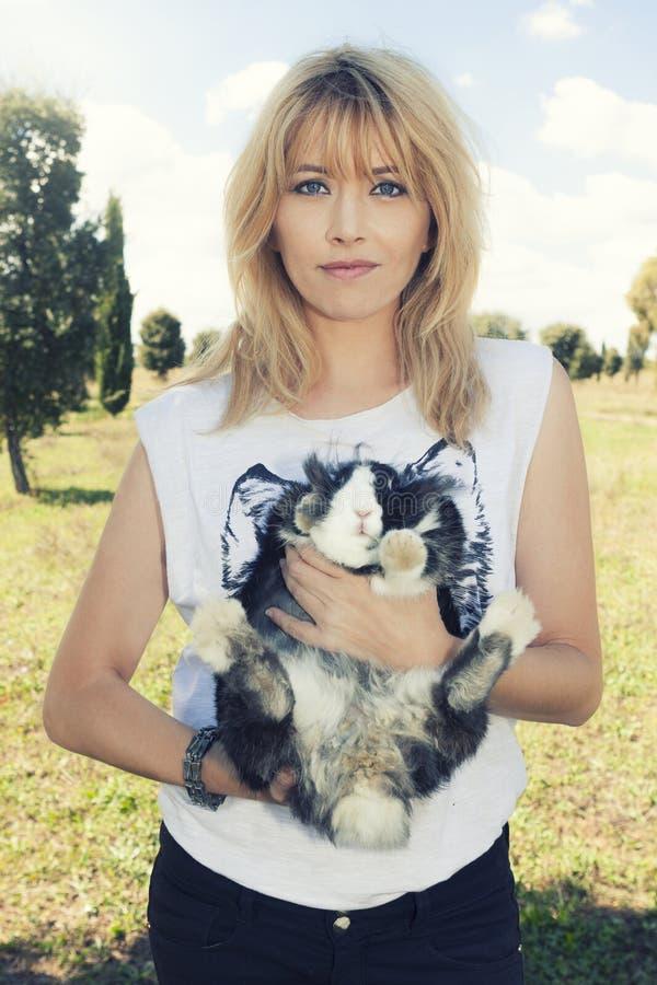 Bella donna dei capelli biondi che tiene il coniglietto sveglio dell'animale domestico fotografia stock libera da diritti