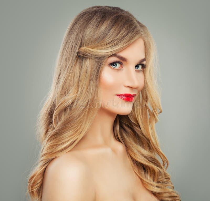 Bella donna dei capelli biondi con capelli ondulati lunghi e trucco rosso delle labbra Bellezza affascinante fotografie stock libere da diritti