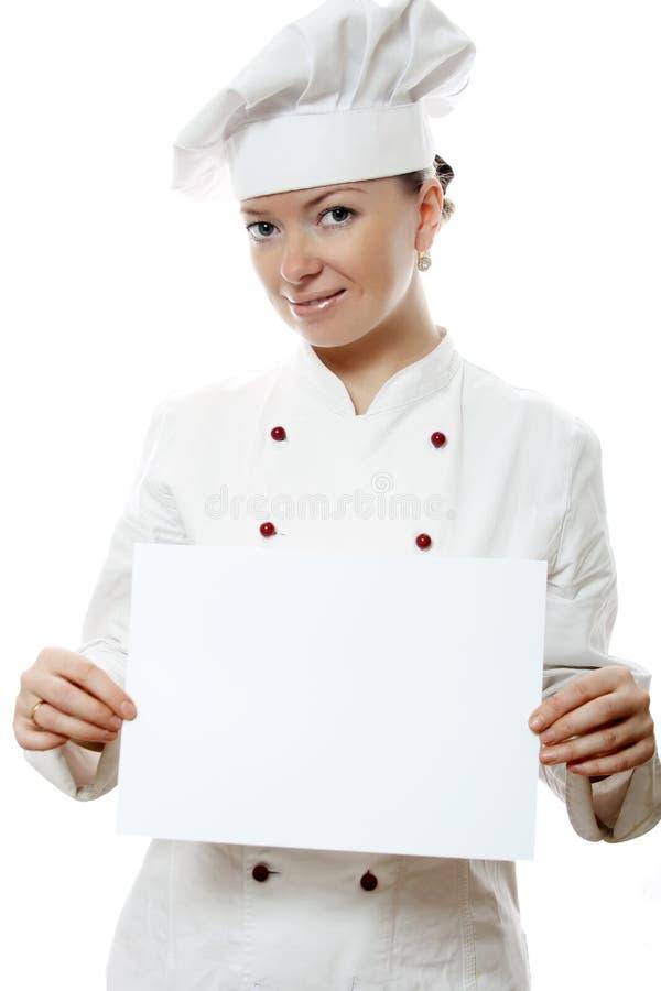 Bella donna del cuoco che tiene una scheda di avviso immagini stock