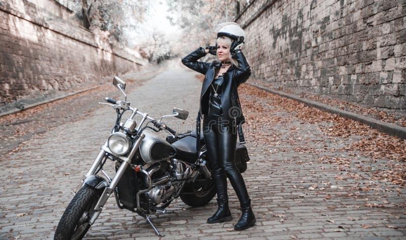 Bella donna del motociclista all'aperto con il motociclo fotografia stock libera da diritti
