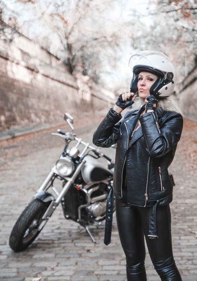Bella donna del motociclista all'aperto con il motociclo immagini stock