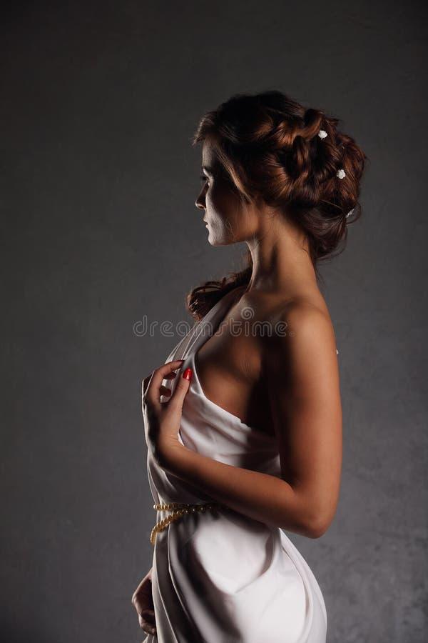 Bella donna del ritratto con il fondo bianco elegante della parete di lerciume del vestito fotografie stock