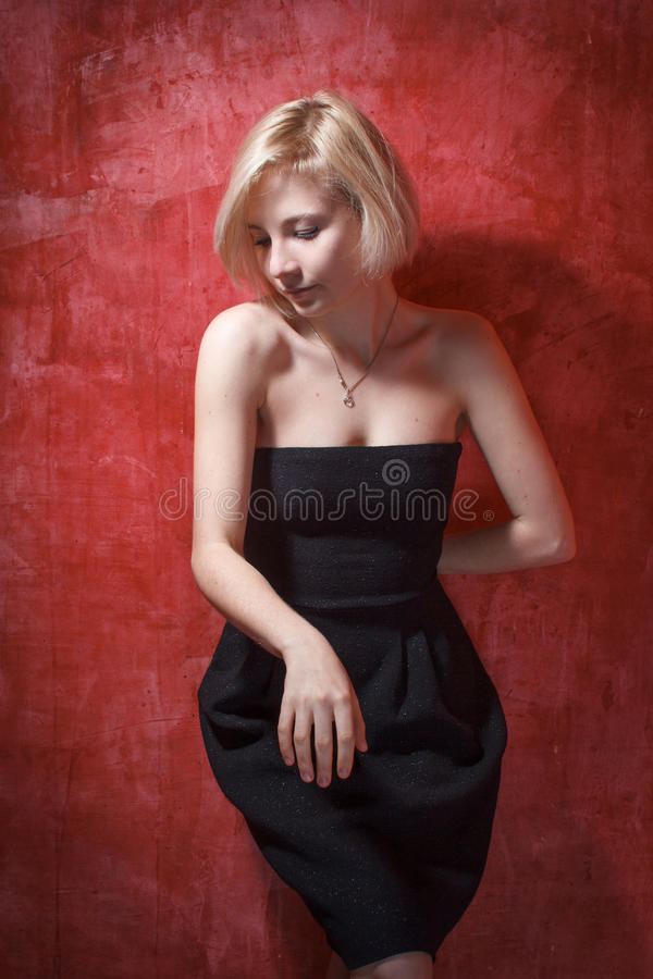 Bella donna del ritratto in vestito sulla parete di lerciume fotografia stock
