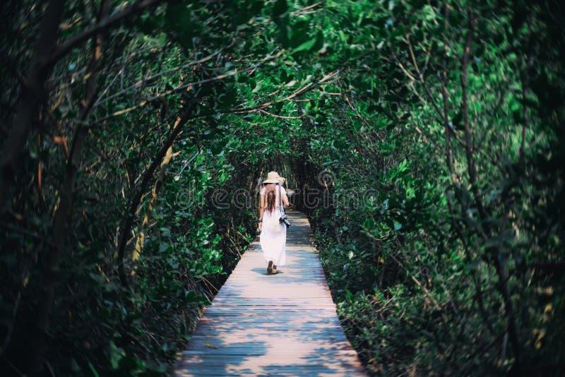Bella donna del viaggiatore in cappello bianco del vestito, della scarpa da tennis e di paglia immagine stock libera da diritti