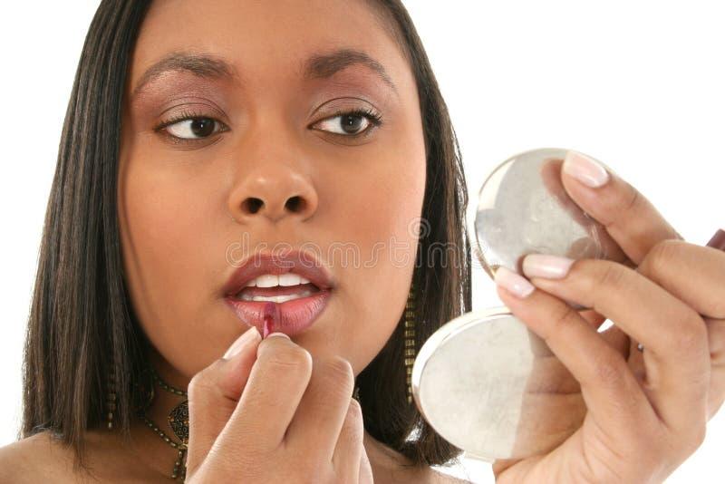 Bella donna dell'afroamericano che mette su Lipgloss fotografia stock libera da diritti