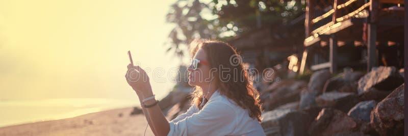 Bella donna della ragazza che si siede sulla spiaggia al tramonto in cuffie e che ascolta la musica, il resto e le feste immagine stock