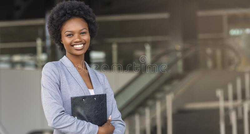 Bella donna di affari di afro che tiene una cartella, esaminante macchina fotografica fotografia stock libera da diritti