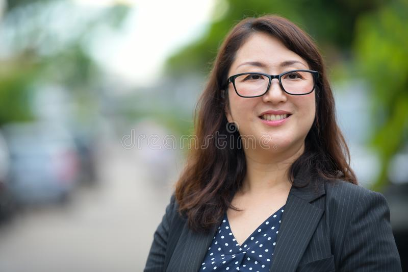 Bella donna di affari asiatica felice matura che sorride e che pensa nelle vie all'aperto immagini stock libere da diritti