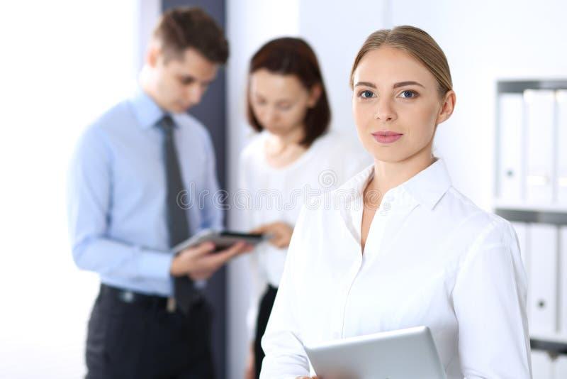 Bella donna di affari bionda che sta diritto in un ufficio brillantemente acceso ai precedenti dei colleghi o dei partner immagine stock libera da diritti