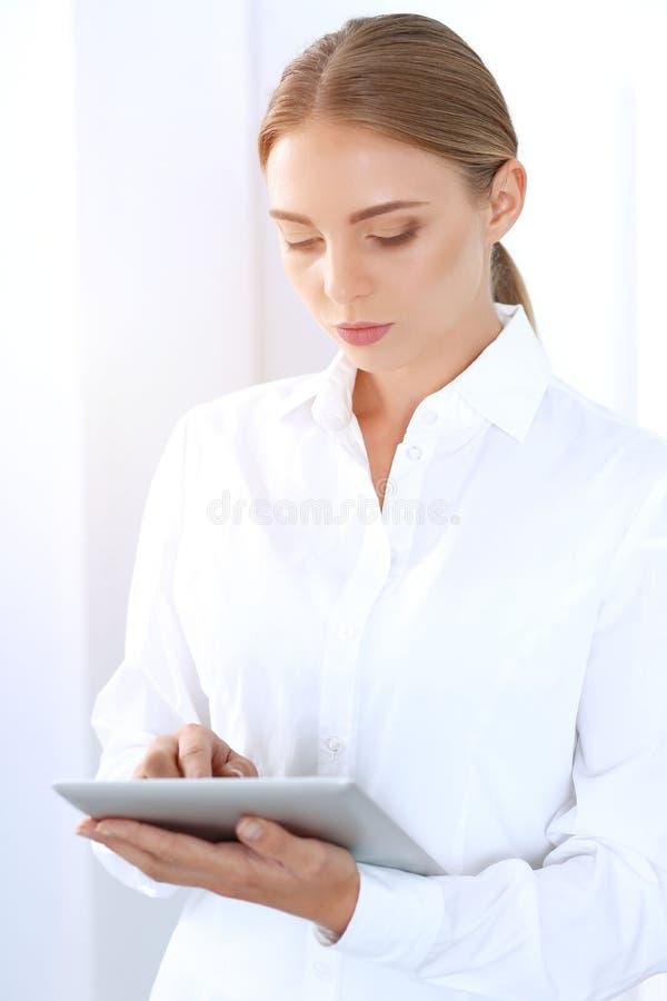 Bella donna di affari bionda che utilizza il pc della compressa mentre stando diritto in un ufficio brillantemente acceso Concett fotografie stock