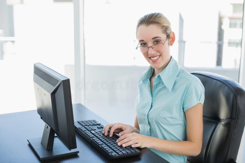 Bella donna di affari calma che lavora al suo computer che sorride alla macchina fotografica fotografie stock
